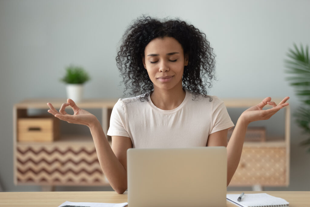 Woman meditating at desk with open laptop